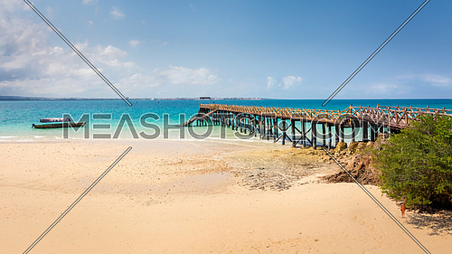 Pictured turquoise Indian Ocean and a beautiful wooden pier built on the shores of Prison Island in Zanzibar, Tanzania