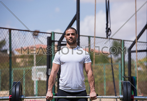 young middle eastern man athlete exercise weightlifting Napoljun on a sunny day