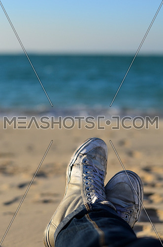 sitting on the beach enjoying time and relaxing wearing shoes and jeans