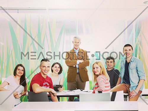 portrait of confident teacher in school classroom,  students group on class in background