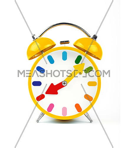 Close up one vivid yellow retro alarm clock with twin metal bells isolated on white background, low angle front view