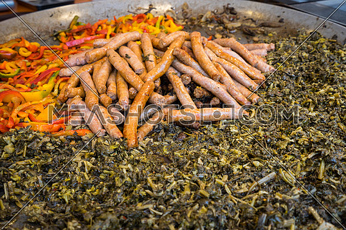 Typical dish of Puglia with sausage, turnip top and peppers, prepared in a large pot during a food fair