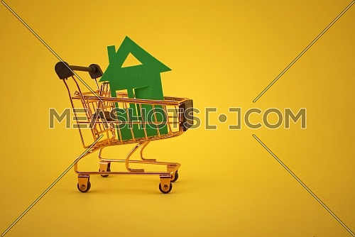 Buy real estate concept with house and shopping cart in the yellow background