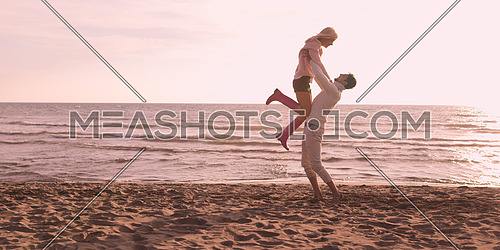 Young couple having fun on beach during autumn sunny day